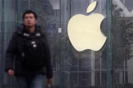 A man walks in front of a company logo outside an Apple store in downtown Shanghai