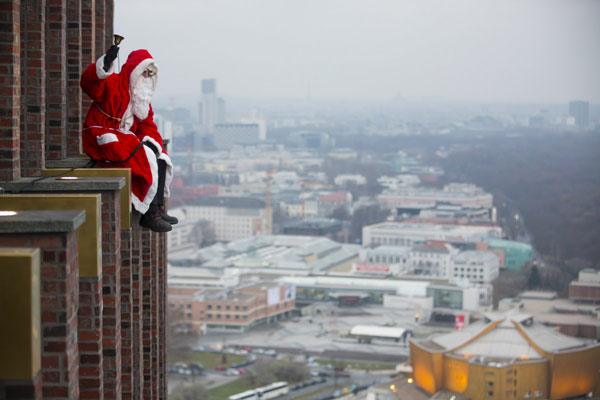 a-man-dressed-as-a-santa-claus-poses-at-the-front-of-the-kollhoff-tower-at-potsdamer-platz-square-in-berlin