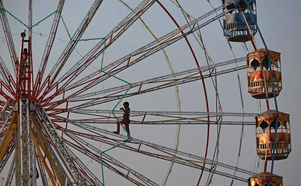 a-worker-installs-lights-while-standing-on-a-ferris-wheel-at-a-fair-in-mumbai