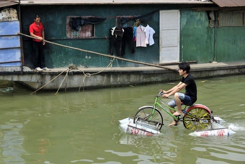 lei-zhiqian-rides-a-modified-bicycle-across-the-hanjiang-river-a-tributary-of-the-yangtze-river-in-wuhan-hubei-province-june-16-2010