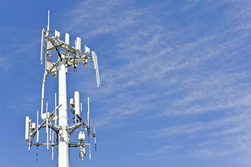Cell phone telecommunication tower with wispy clouds
