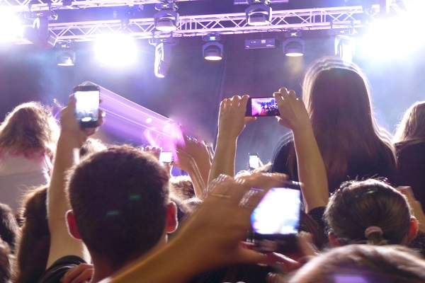 Crowd of fans at a live concert performance on a night out photographing the band on their mobile phones and cheering , view from the back
